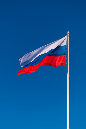The Russian flag on the flagpole fluttering in the wind on blue sky background. Tula, Russia Standard-Bild