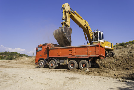 Yellow excavator on the construction site loads the soil into the body of a red dump truck. Banque d'images
