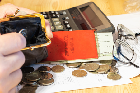 Hand pensioner, glasses, calculator and wallet with coins on the surface of the table. Translation of the inscription: pensioners Certificate Reklamní fotografie