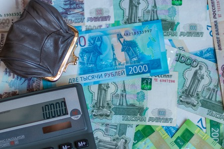 Russian rubles, wallet with small coins and calculator are on the table.
