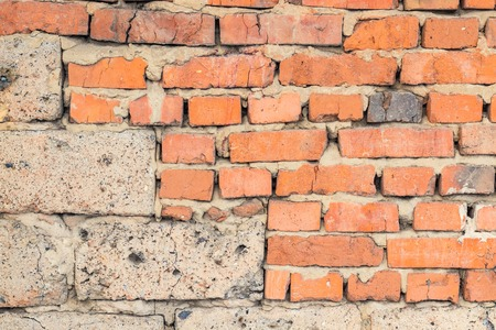 A wall of old worn red brick, as a background Stock Photo