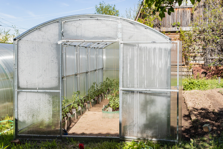 Greenhouse made of polycarbonate on a country plot. Tula region Russia Banco de Imagens - 123937021