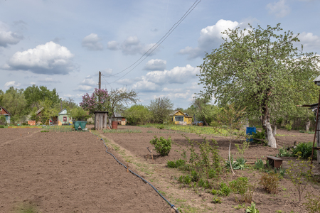 Country house with cultivated land surrounded by greenery in spring in Russia, Russian dacha.