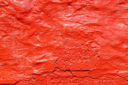 Old plastered wall painted with fresh red paint. Abstract background of red walls, close up