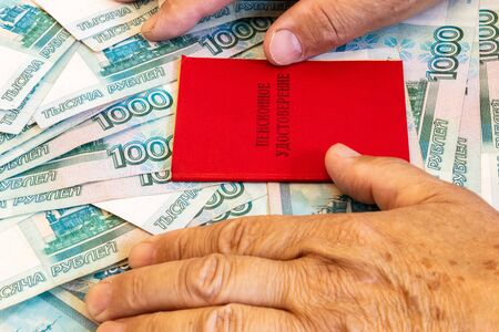 pension certificate and pensioners hands are on the bills in 1000 rubles, The inscription on the certificate: pension certificate Banco de Imagens