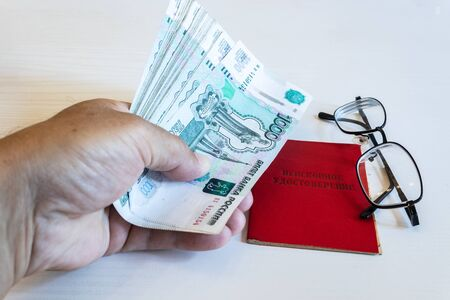 pension certificate, banknotes of 1000 rubles, the hands of a pensioner, The inscription on the certificate: pension certificate Banco de Imagens
