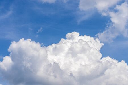 A big white cloud in the blue sky on a beautiful Sunny day, as a background