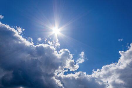 Il sole e una nuvola bianca nel cielo azzurro in una bella giornata estiva, come sfondo