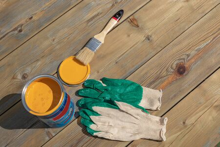 a can of yellow paint with a brush and gloves, ready to paint. repair and renovation concept. top view Stockfoto