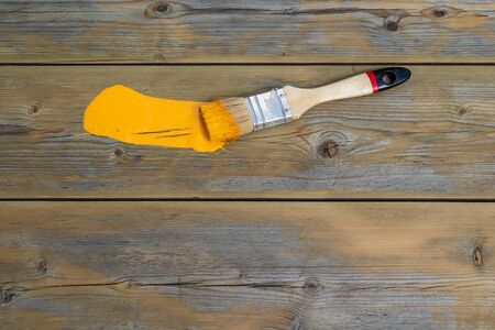 painting brush is on a wooden surface. a brushstroke. repair and renovation concept. top view