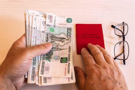certificado de pensión, billetes de 1000 rublos, las manos de un pensionista, La inscripción en el certificado: 'certificado de pensión'
