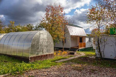 suburban suburban area with a house and greenhouses made of polycarbonate. Early autumn. Tula region Russia