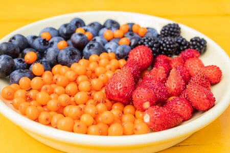 Mixed various berries collected on the plot, assorted berries of blackberries, strawberries, blueberries, sea buckthorn. Colorful and healthy concept. Black, blue, red, green. close up Stock Photo