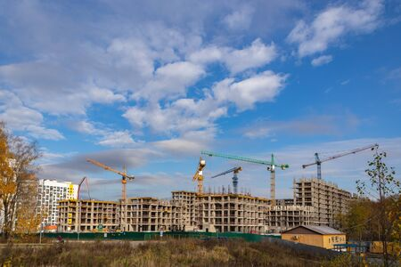 Construction of the third stage of a new residential complex in the forest. Work construction cranes, is the construction of walls of buildings. Moscow, Russia