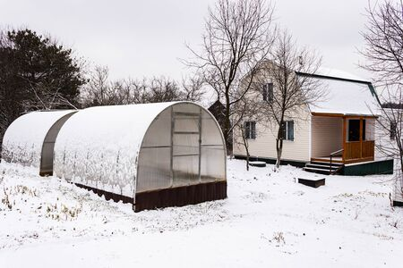 suburban suburban area with a house and greenhouses made of polycarbonate. Early winter. Tula region, Russia Banco de Imagens