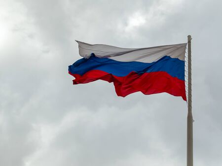 Russian flag flying on a flagpole in a strong wind. symbol of patriotism. Tula. Russia