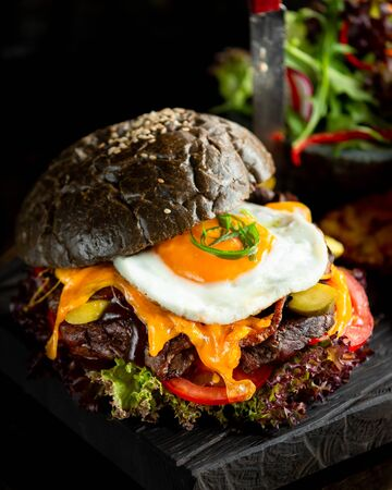 Black burger with meat cheese vegetables and fried eggs