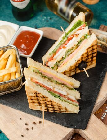 Classic club sandwich with fries and sauce Stockfoto