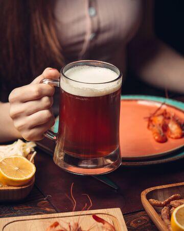 Red beer mug with shrimps and lemon Фото со стока