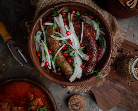 Georgian kupat with onions and pomegranate in earthenware Stok Fotoğraf