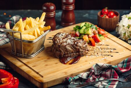 Beef steak with pomegranate sauce, french fries and fresh salad