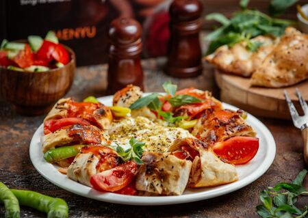 Beyti wrapped kebab topped with tomato sauce, served with tomato, pepper, yoghurt