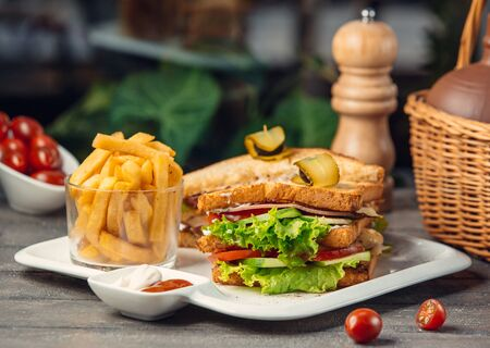 Club sandwich with lettuce, tomato, cucumber, turkey breast, fries Stockfoto