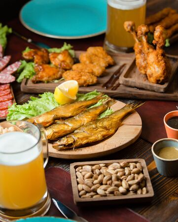 Dried smoked fish as beer snack with nuggets, beer, pistachio