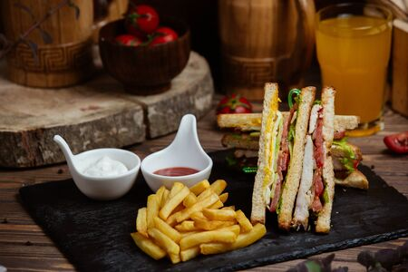 Club sandwich with chicken, tomato, cheese, lettuce, cucumber, fries and mayo