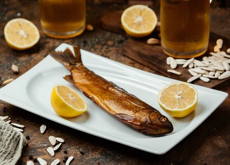 Dried smoked fish served with lemon halves, salty sunflower seeds and beer Фото со стока