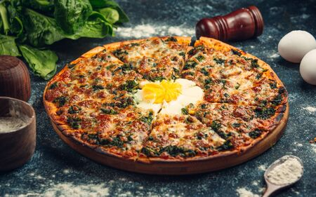 Breakfast pizza with pesto sauce and sunny side up egg in the middle Stock fotó