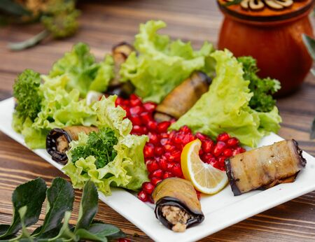 Fried aubergine wraps with minced meat and fresh herbs, lemon, lettuce, pomegranate