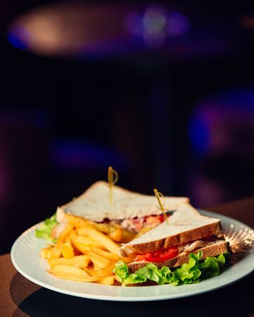 Club sandwich with chicken, tomato, lettuce, served with french fries Stockfoto