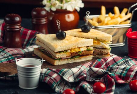 Club sandwich with eggs, lettuce, salami, cucumber, tomato, served with fries Stockfoto