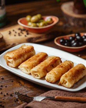 Fried meat wraps as a side dish for dinner with olives Stockfoto