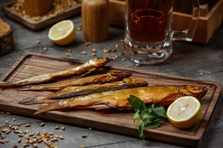 Dried smoked fish served with lemon on wooden board for beer night