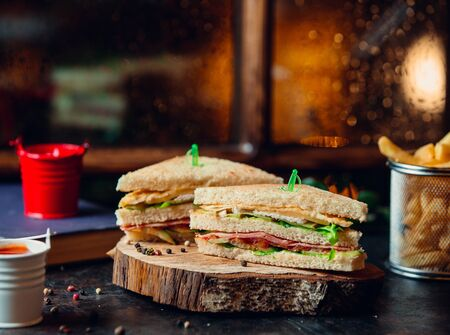 Club sandwich with ham, lettuce, tomato, cheese, and fries on wooden board