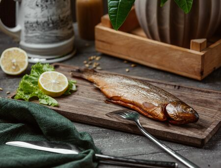 Dried smoked fish served with lemon slices on wooden board