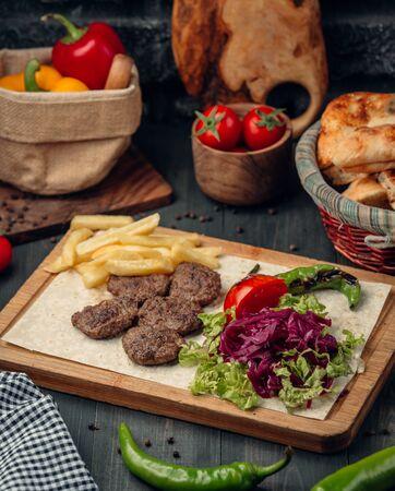 Polpette di carne servite con patatine fritte e insalata verde