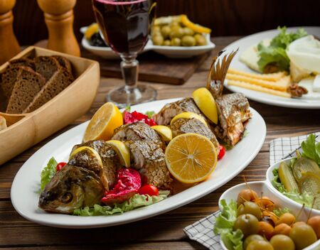 Roasted fish served with lemons and pomegranate with cheese plate