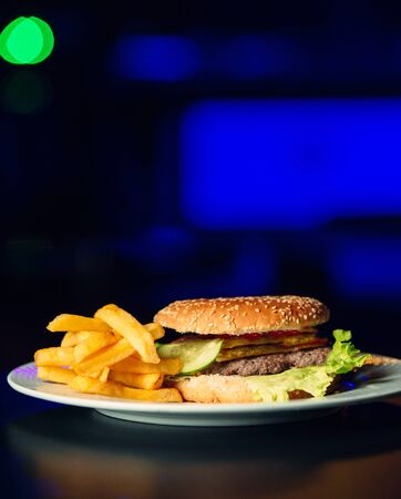 A plate of burger with beef patty, lettuce, tomato, cucumber and fries