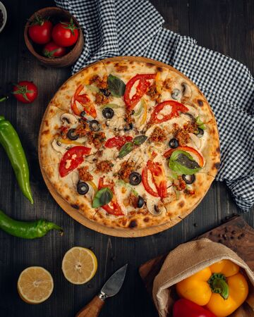 Mix pizza with tomato slices, mushroom, olive, basil leaves, and minced meat