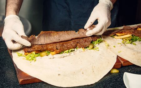 Man putting thinly cut doner meat into fladbread with fries, lettuce Фото со стока