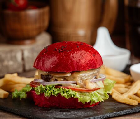 A close up of red burger with lettuce, onion, melted cheese