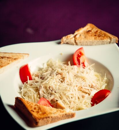 A close up of plate with roasted chichken with grated parmesan cheese and fresh tomatos Stockfoto