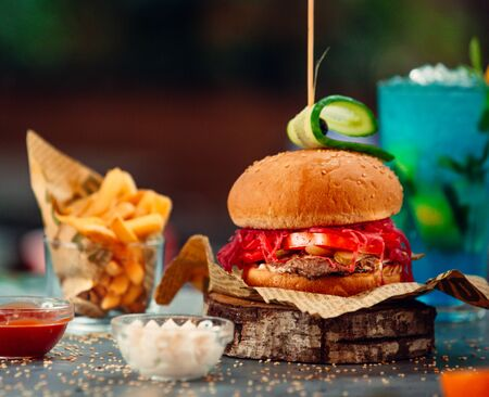 Small beef burger with red pickled cabbage, tomato, cucumber and fries