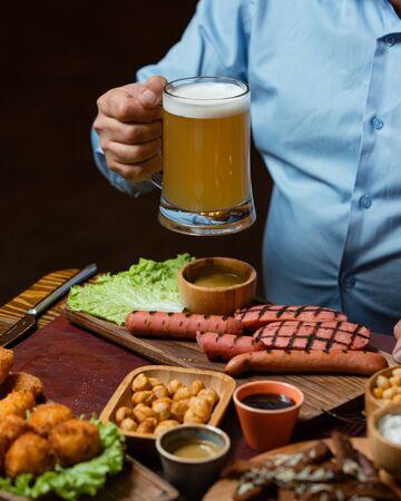 Man holding beer mug served with grilled sausages, chickpeas, crispy meatballs