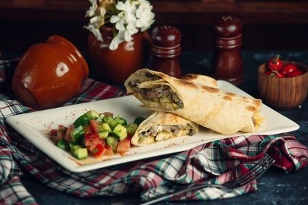 Shawarma wrap with meat, french fries, pickled cucumber and salad