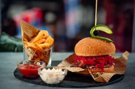 Small beef burger with pickled red cabbage, tomato, fries and sauces