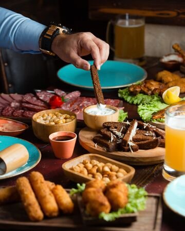 Man dipping black bread strip into yoghurt served with croquettes, beer, sausages Фото со стока